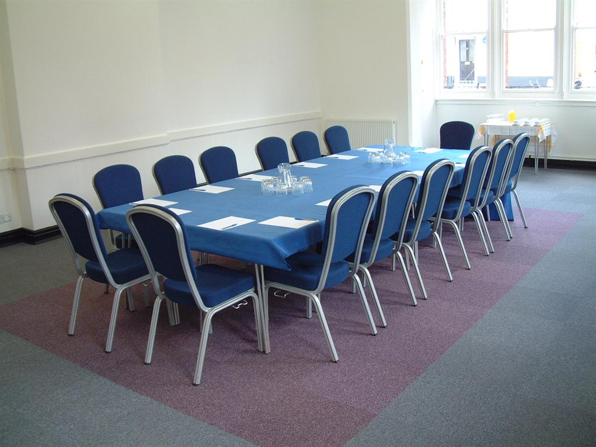 tables and chairs set up for a meeting in a wide room with a big window at one end