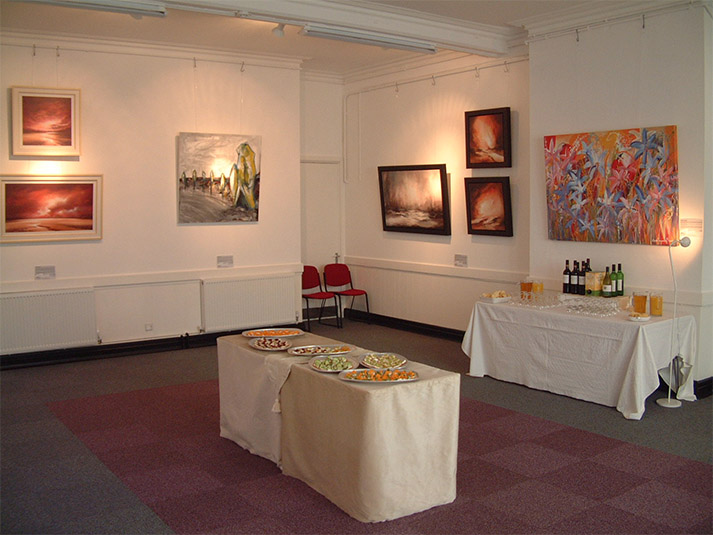 exhibition of paintings and a table of food in a spacious room